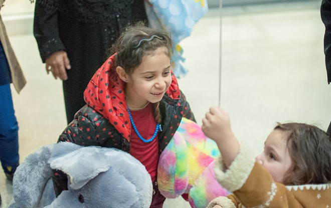 Iraqi refugee Rahaf Al-Sawaedi, holding two giant stuffed animals, meets her little cousin for the first time. - DANIEL WALTERS PHOTO