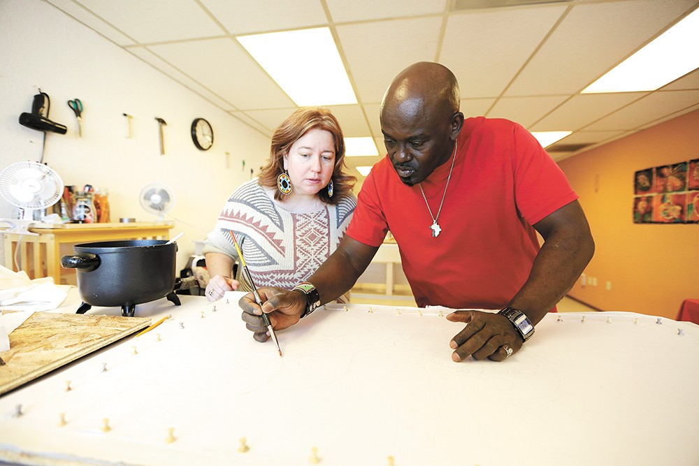 Sironka instructs student Lynn Lovato on applying wax to fabric to make a batik. - YOUNG KWAK