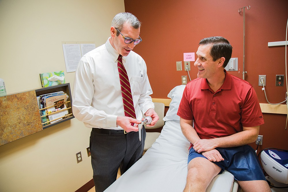 Dr. Kirk Riechard, left, explains the mechanics of hip replacement to patient Paul Kimball. - JENNIFER DEBARROS