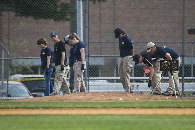 Members of the FBI Evidence Response Team search the field where House Majority Whip Steve Scalise (R-La.) was shoot during a congressional baseball practice at Eugene Simpson Stadium Park in Alexandria, Va., June 14, 2017. After a gunman opened fire on Republicans practicing baseball, lawmakers are pressing to lift regulations on silencers and allow members to carry guns. - AL DRAGO/THE NEW YORK TIMES