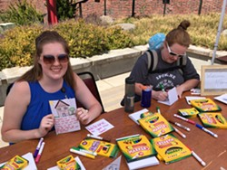 Jessica Fisher, left, and Sarah Miller make Welcome Home cards for move-in kits for youths who have been placed in housing.