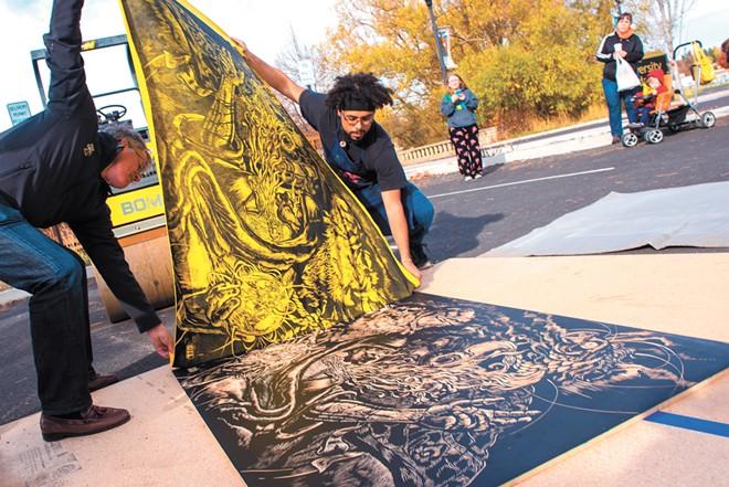 Reinaldo Gil Zambrano, left, an art instructor, created prints using a steamroller last fall. - JOSEPH PALLEN/UNIVERSITY OF IDAHO