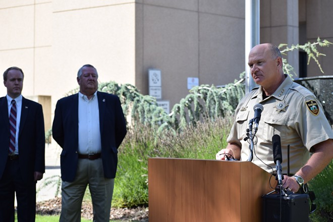 Spokane County Commissioners Josh Kerns, left, and Al French listen to County Sheriff Ozzie Knezovich speak at a press conference last month. - WILSON CRISCIONE PHOTO