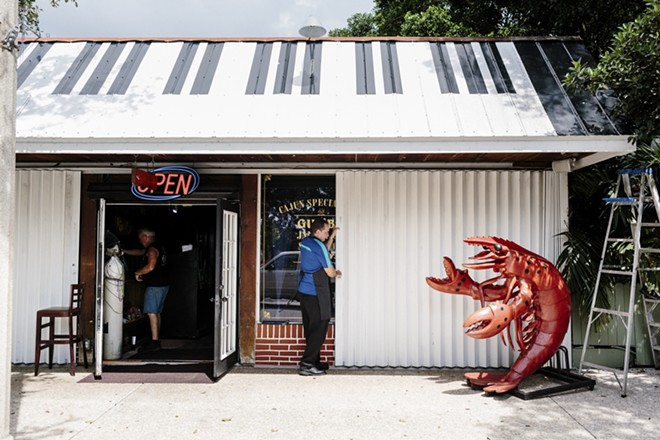 """Mark Kren closes the storm shutters at Crawdaddy's, his restaurant in Jensen Beach, Fla., Sept. 8, 2017. Gov. Rick Scott of Florida said Hurricane Irma would be """"way bigger than Andrew,"""" warning hundreds of thousands of people in its path to flee. - JASON HENRY/THE NEW YORK TIMES"""