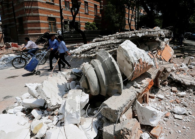 People walk next to debris after an earthquake in Mexico City on Tuesday.