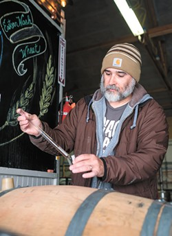 Alex Wilbur at work in the Savage Boar distillery in Airway Heights. - HECTOR AIZON
