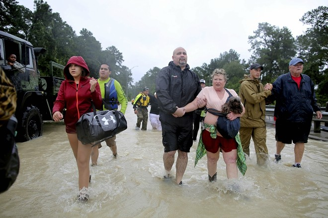 Volunteer and rescue officials help residents to safety after they had to be rescued by boats from their homes after the area flooded in Houston, Aug. 29, 2017. - BARBARA DAVIDSON/THE NEW YORK TIMES