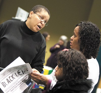 The editor and publisher of the Black Lens, Sandy Williams, left, speaks with Charlotte Lewis and her daughter at a Martin Luther King, Jr. Day rally. - YOUNG KWAK