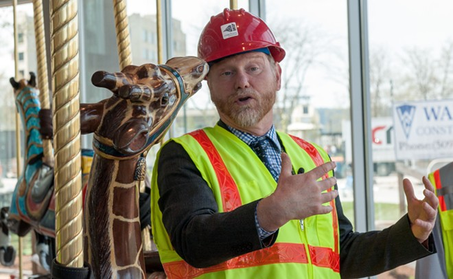 Spokane Parks director Leroy Eadie attempts to concentrate on talking about the park while a Carrousel giraffe tries to make out with him. - DANIEL WALTERS PHOTO
