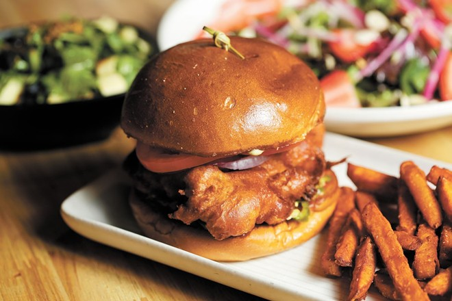 The waffle chicken sandwich, shown here with a side of sweet potato fries, is an early favorite at Bark, A Rescue Pub.
