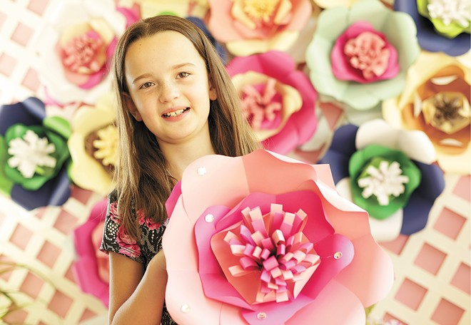Keira Larson, 9, with paper flowers that she and her family make and sell; proceeds support local animal shelters.