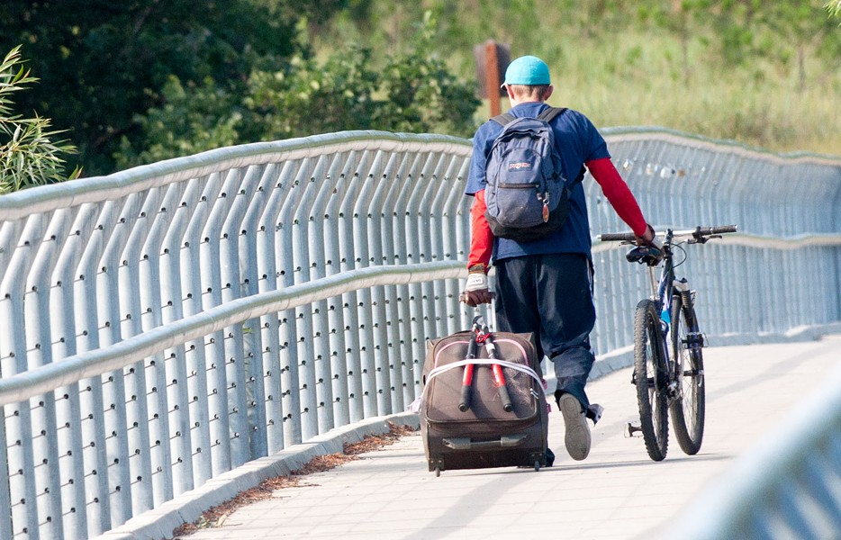 A gentleman drags a bicycle and rolling suitcase with lopping shears strapped to the back over Sandifur Bridge on the morning of Friday, June 29. - DANIEL WALTERS PHOTO