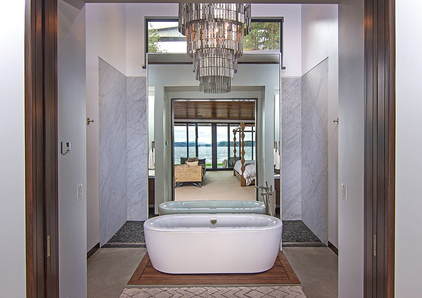 "A mirror behind the bathtub, which sits on a ""raft"" of teak flooring, brings lake views into focus from any direction. - JOEL RINER PHOTO"
