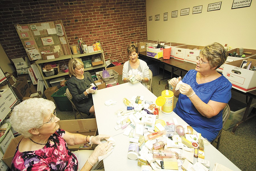 Volunteers with Project Beauty Share organize donated personal-care items. - YOUNG KWAK