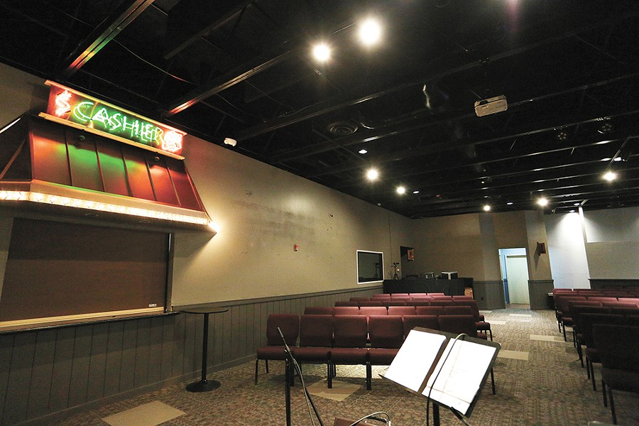 The interior of Uplift Church, with the cashier sign from its days as a Hooters. - YOUNG KWAK
