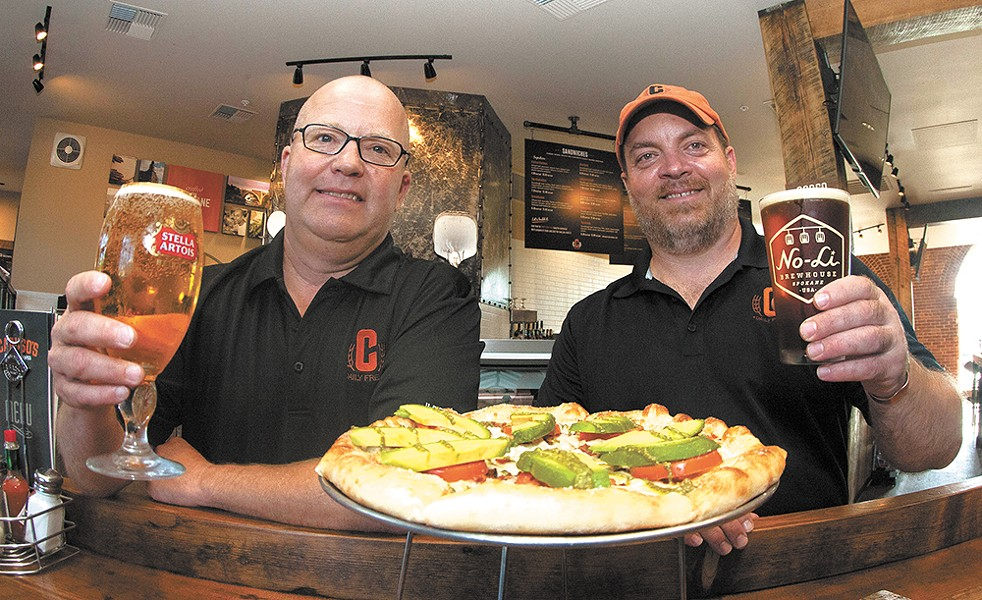Caruso's Jay Jordan and Vince Caruso celebrate the opening with a cold beer and the Tuscan pizza. - MEGHAN KIRK