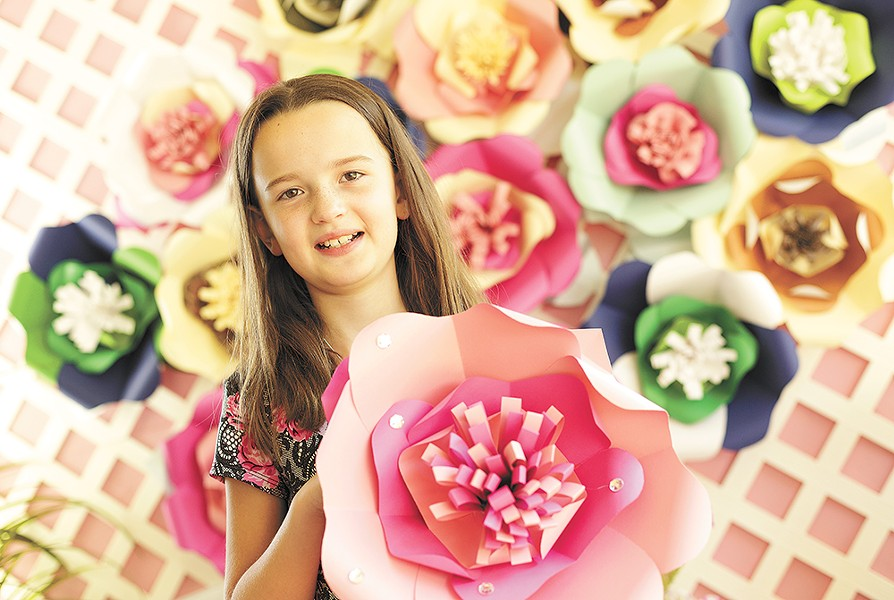 Keira Larson, 9, with paper flowers that she and her family make and sell; proceeds support local animal shelters. - YOUNG KWAK