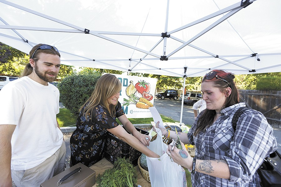 Food For All farm manager Whitney Jacques (center) and volunteer John Jozwiak (left) sell produce at the Emerson Garfield farmers market. - YOUNG KWAK