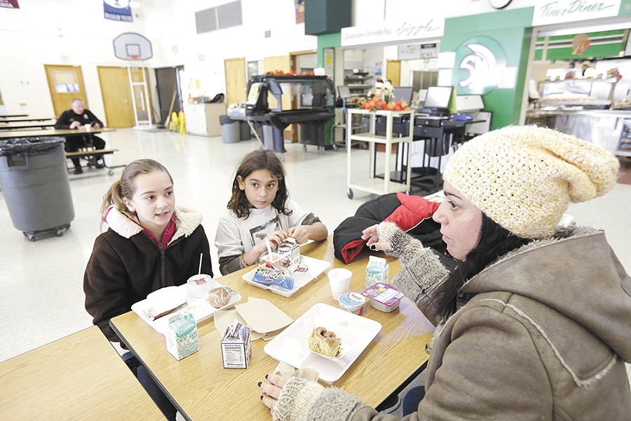 On Nov. 25, Alisa Vashon and her children, Arona and Arlis, eat a meal at the Salk Middle School warming center, regaling each other with stories about the windstorm. - YOUNG KWAK