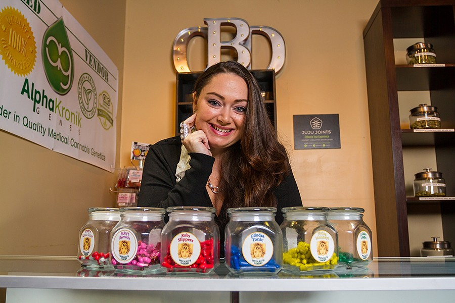Northside Alternative Wellness Center manager Katie Beaman stocks a line of CBD capsules called Wizard's Garden. - KRISTEN BLACK