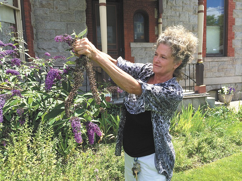 Mary Moltke tidies up the garden of her historic Browne's Addition mansion that she now rents out for events. - MITCH RYALS