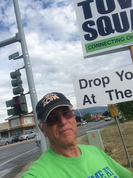 Liberty Lake Mayor Steve Peterson on the street holding a sign advocating for the Town Square Project.