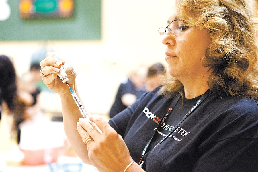 LaDon Gill, a health care worker, fills a syringe at the Greenacres Middle School immunization clinic. - KRISTEN BLACK