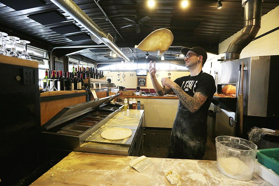 South Perry Pizza cook Nate Coyne rounds dough by tossing it into the air. - YOUNG KWAK