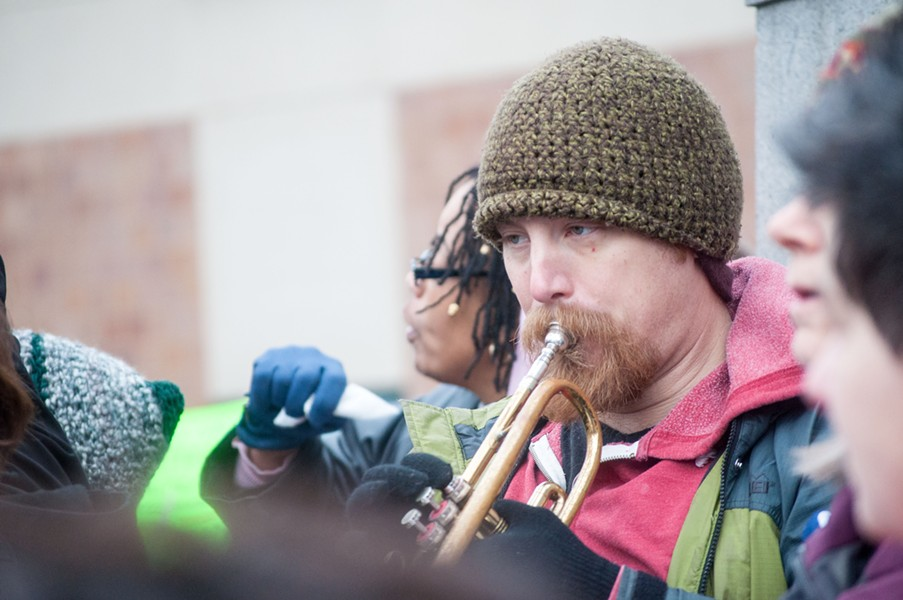 Jon Lossing plays the trumpet to the beat of protester chants. - DANIEL WALTERS PHOTO