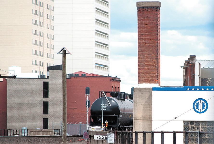 An oil train car passes through downtown Spokane. A consultant hired by the city warned that the city's elevated tracks could lead to a scenario where a train car full of explosive oil derails and lands on top of a building. - DANIEL WALTERS