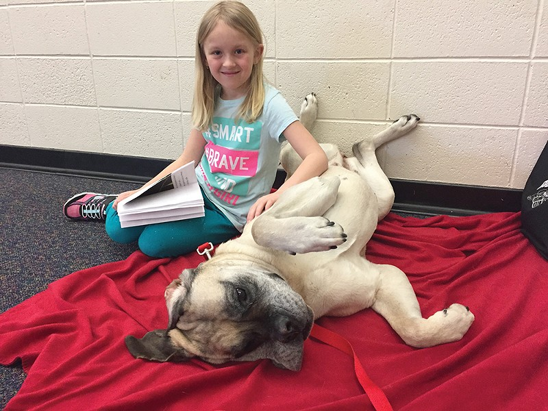 Ellee is ready for a belly rub during a Reading Rover session with Kayden at Windsor Elementary in Cheney.