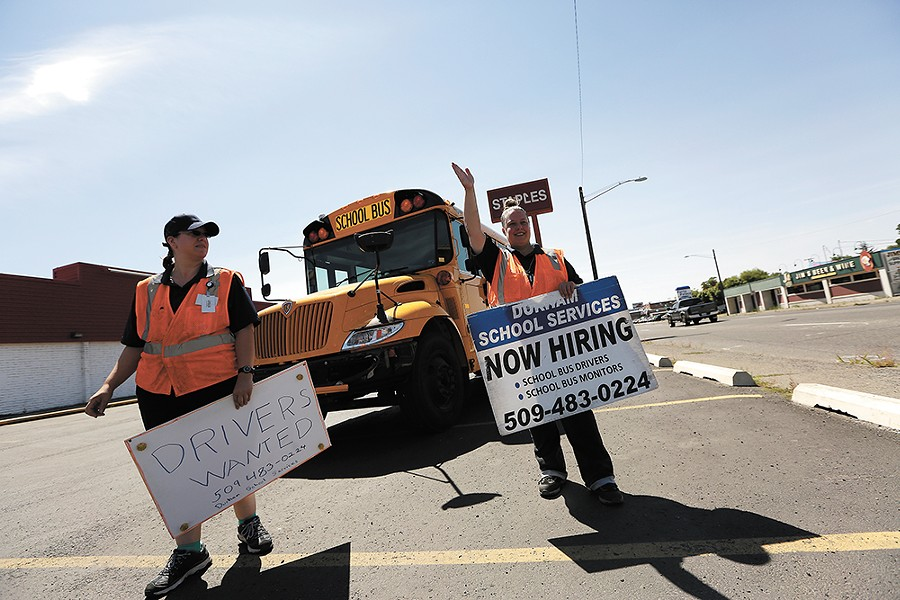 Durham School Services employees, like Kacey Waddell, left, and Christy Lamberson, spend hours at busy intersections in search of the next batch of school bus drivers. - YOUNG KWAK
