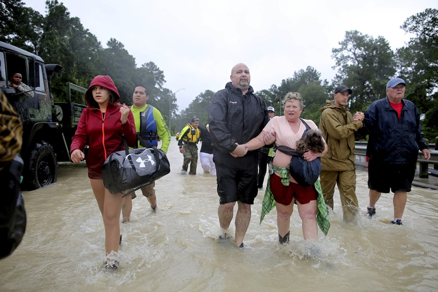 Volunteer and rescue officials help residents to safety after they had to be rescued by boats from their homes after the area flooded in Houston, Aug. 29, 2017. As one of the most destructive storms in the nation's history pummeled southeast Texas for a fourth day, forecasts on Tuesday called for still more rain, making clear that catastrophic flooding that had turned neighborhoods into lakes was just the start of a disaster that would take years to overcome. - BARBARA DAVIDSON/THE NEW YORK TIMES