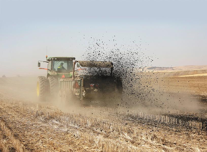 Kevin Johnbrow, from Spokane's wastewater treatment plant, spreads biosolids on a farm near Reardan last week. - YOUNG KWAK