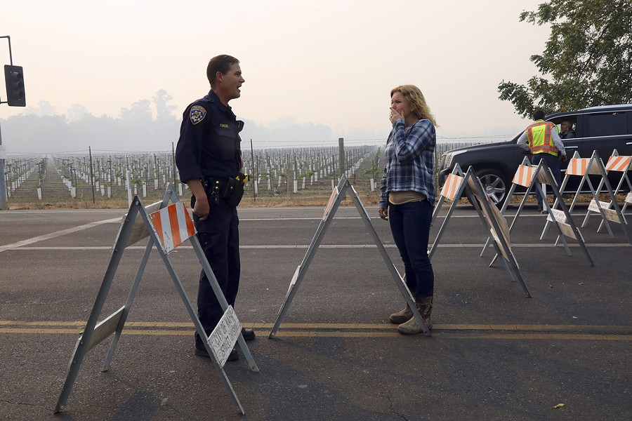 A woman pleads with a California Highway Patrol officer to allow her through a roadblock to an area damaged by wildfires in Napa, Calif., Oct. 10, 2017. - JIM WILSON/THE NEW YORK TIMES