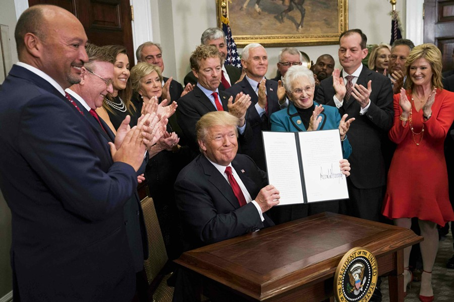 President Donald Trump signs an executive order that clears the way for potentially sweeping changes in health insurance, during an event attended by small-business owners and others at the White House, in Washington, Oct. 12, 2017. - DOUG MILLS/THE NEW YORK TIMES