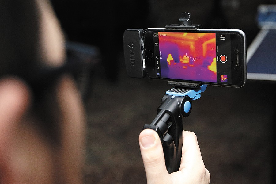 Jacob Lusk uses a FLIR thermal camera attachment during a recent paranormal investigation. - YOUNG KWAK