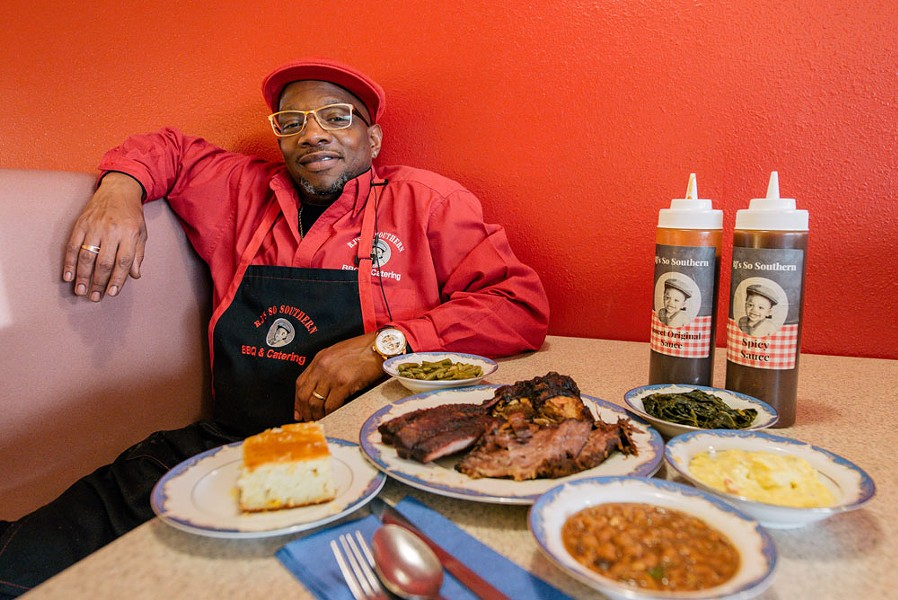 Reggie Perkins sits with some of his Nashville-inspired cuisine at his North Spokane barbecue spot. - ERICK DOXEY