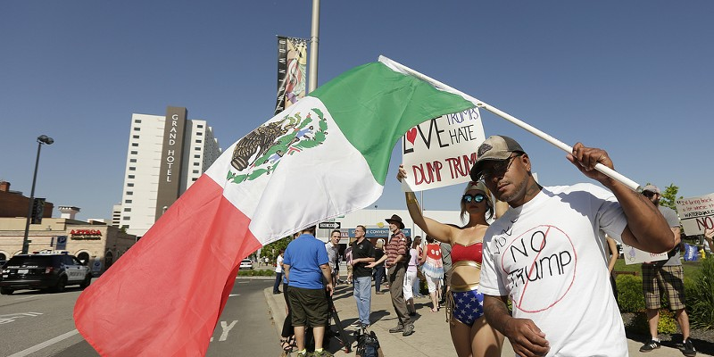 Scenes from Donald Trump's Campaign Rally in Spokane Vince Flores, right, holds a Mexican flag as Cam Zorruzua, both opponents of Republican presidential candidate Donald Trump holds a sign before a campaign rally. Young Kwak