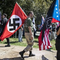 "Clashes in Charlottesville A white nationalist carries a Nazi flag during a protest in Charlottesville, Va., Aug. 12, 2017. The White House, under siege over President Trump's initial comments, on Sunday condemned ""white supremacists"" for inciting violence that left a woman dead Saturday. Matt Eich/The New York Times"