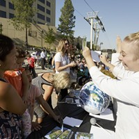 Partial Solar Eclipse in Spokane Mobius Science Center Education Manager Kelli Crawford, right, shows Michele Sapronetti, left, who's holding her 2 1/2 year old daughter Milissa Sapronetti and her 8 year old daughter Mikayla Sapronetti how a pinhole viewer at the Spokane Tribal Gathering Place before solar eclipse.