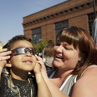 Partial Solar Eclipse in Spokane Jessica Barnes, holds solar glasses for her 5 year old son Donovan Hogan, who looks at a partial solar eclipse, at the Spokane Tribal Gathering Place. Young Kwak
