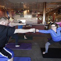 Boga Instructor Sara Murphy, right, and Kevin Buck stretch out their beers during a Boga class at Badass Backyard Brewing in Spokane Valley. Young Kwak