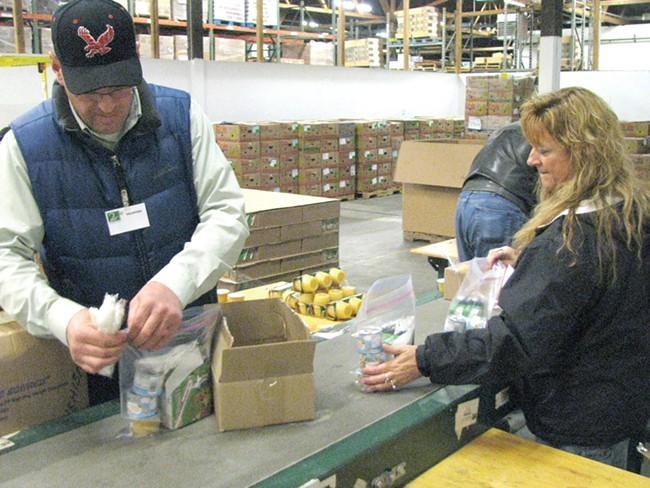 In a 2011 photo, volunteers pack food into boxes for the Second Harvest Food Bank.