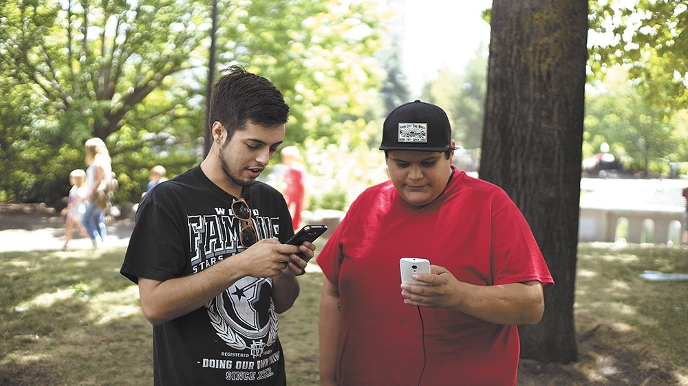 Tyler Zoesch (left) and Daniel Moreno on the hunt for Pokémon Go characters at Riverfront Park. - ANDRA MOYE