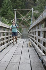 Megan Ferney walks with her almost 1-year-old cat Leon on the Bowl and Pitcher suspension bridge at Riverside State Park in Spokane, Wash., Friday, June 15, 2018. (Young Kwak/The Inlander)