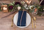 Signer employs basic tableware to make sure flowers get all the attention on this rustic table, which was crafted from salvaged planks by the homeowners Justin and Tarah Gray.