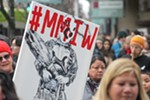 """A marcher holds a sign with that reads #MMIW, for the hashtag """"murdered and missing indigenous women."""""""