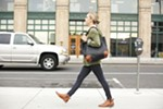 Leather maker Teddi Cripps walks downtown Spokane with her black and cognac Weekender bag in hand.