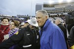 Washington Governor Jay Inslee walks towards a stage to award the Apple Cup trophy to Washington.